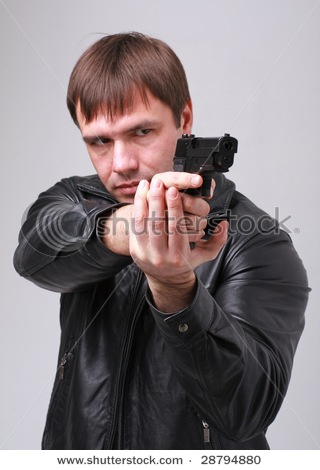 stock-photo-aiming-serious-man-with-a-gun-on-a-gray-background-28794880.jpg.17ad4fd4aa2c8037497f4a65d62ef238.jpg